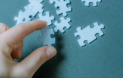 Puzzle piece in hand. Searching Puzzle piece coming down into it`s place. Solution concept. Blue background Royalty Free Stock Photo