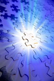 Puzzle pieces. Jigsaw puzzle pieces. One brightly lit. Blue tone stock photography