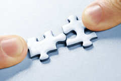 Puzzle pieces. Fingers pushing two matching puzzle pieces together royalty free stock image