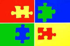 Puzzle pieces. Four coloured puzzle pieces on coloured background royalty free stock photo