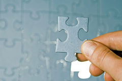 Puzzle pieces. Inserting last piece of puzzle Royalty Free Stock Images