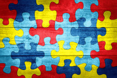 Puzzle Pieces in Autism Awareness Colors Background Illustration. A colorful autism awareness puzzle background with wood texture illustration royalty free illustration