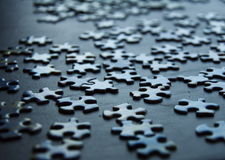 Puzzle Pieces Background. A puzzle lays on a table in chaotic randomness.  The pieces shine in the light of a nearby window.  Show with intentional shallow depth Royalty Free Stock Photography