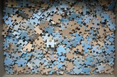 Puzzle pieces in the box mostly blue and white colors. Disassembled puzzle in the box royalty free stock photos