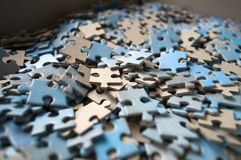 Puzzle pieces close up mostly blue color. Selective focus. Pieces of a puzzle in a box royalty free stock photos