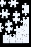 Puzzle pieces coming together. Against a black background stock photography