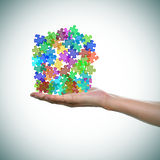 Puzzle pieces of different colors as the symbol for the autism a. A man hand with a pile of puzzle pieces of different colors as the symbol for the autism Stock Photography