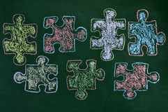 Puzzle pieces of different colors drawn on a chalkboard, as the. Some puzzle pieces drawn with chalk of different colors on a green chalkboard, as the symbol for Royalty Free Stock Photography