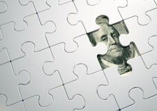 Puzzle pieces on dollar Royalty Free Stock Image