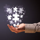 Puzzle pieces in the hand of a businessman Royalty Free Stock Photography