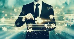 Puzzle pieces with man holding a tablet Stock Images