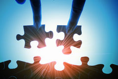 Puzzle pieces. Puzzle piece coming down into its place royalty free stock photo