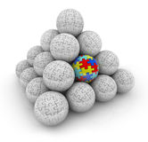 Puzzle Pieces Pyramid Balls One Unique Special Autistic Standing. A pyramid of balls with puzzle pieces on them and one with colored pieces as a symbol of autism Royalty Free Stock Image