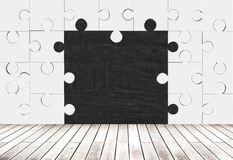 Puzzle pieces room and blackboard. Blank blackboard in room made of puzzle pieces with wooden floor. Concept of missing pieces. Mock up Royalty Free Stock Photography