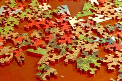 Puzzle pieces spread across a dark wood table royalty free stock images