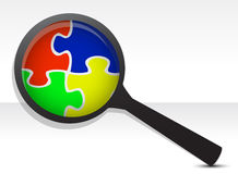 Puzzle pieces under magnifier Royalty Free Stock Images