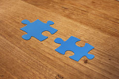 Puzzle pieces on wood table. Blue puzzle on wood table with matching point Royalty Free Stock Photos
