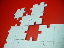 Puzzle on red. White puzzle pieces on red background Royalty Free Stock Image