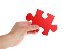 Puzzle. A red puzzle in hand on white background stock image