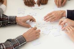 Puzzle se réunissant d'équipe diverse de travail à l'activité teambuilding photographie stock