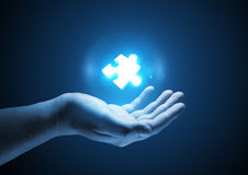 Puzzle Solutions. Conceptual illustration. A man holding a glowing single puzzle piece Stock Photo