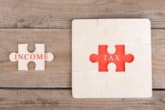 Puzzle-Stücke mit Wörtern u. x22; Tax& x22; und u. x22; Income& x22; lizenzfreies stockbild