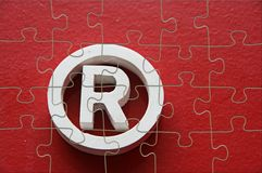 Puzzle of trademark. Puzzle of R - Registered trademark in a red background stock photography