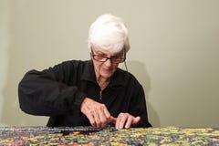 Puzzle un da una donna di eldery Fotografie Stock