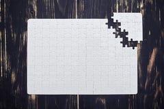 Puzzle vicino al soltion sullo scrittorio di legno scuro Fotografia Stock Libera da Diritti