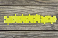 Puzzle on wooden table Stock Photography