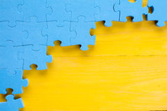 Puzzle on yellow wooden background Royalty Free Stock Images