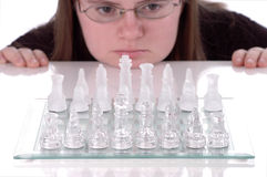 Puzzled. A woman rests her chin against a table and stares at a chess board as she ponders her next move stock images