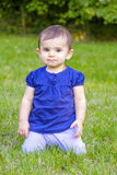 Puzzled baby on knees grass Stock Image