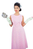 Puzzled black hair model holding a pan and wearing rubber gloves Stock Photography