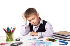 Puzzled borrade elevsammanträde på skrivbordet med handen under huvudet som omgavs med brevpapper Arkivbild