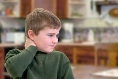 Puzzled Boy. Boy with hand on neck with sad expression Stock Photography