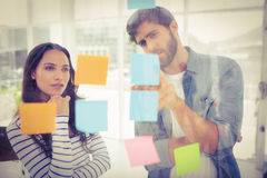 Puzzled business team looking post its on the wall Stock Photos