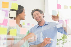 Puzzled business team looking post its on the wall Stock Photo