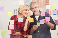 Puzzled business team looking post its on the wall Royalty Free Stock Photos