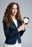 Puzzled business woman holding an alarm clock Stock Photo