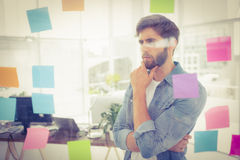 Puzzled businessman looking post its on the wall. In the office stock image