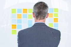 Puzzled businessman looking post its on the wall Royalty Free Stock Photo