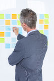 Puzzled businessman looking post its on the wall Stock Photos