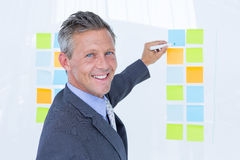 Puzzled businessman looking post its on the wall Stock Image