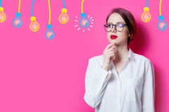 Puzzled businesswoman with abstract lamps Stock Photos