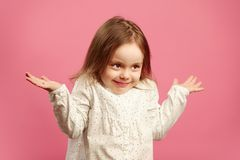 Puzzled child shrugs her shoulders and raises hands, expresses ignorance or difficulty, does not know answer to the. Question. Portrait of doubting little girl Stock Images