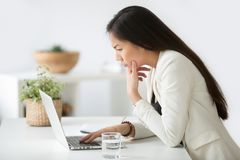 Puzzled confused asian woman thinking hard looking at laptop scr. Puzzled confused asian woman thinking hard concerned about online problem solution looking at stock image