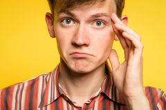 Puzzled confused bewildered pensive man thinking. Of smth. portrait of a young guy on yellow background. emotion facial expression and feelings concept royalty free stock photos