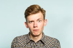 Puzzled confused bewildered shocked amazed man. Comical reaction. portrait of a young guy on light background. emotion facial expression and feelings concept royalty free stock image