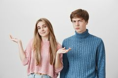 Puzzled confused young couple, female in pink sweater shrugging shoulders, saying so what, not feeling guilty. Frowning. Angry fair-haired male looking with royalty free stock photography